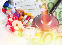 Health care. Splashed one hundred euro bills and pills stock photo