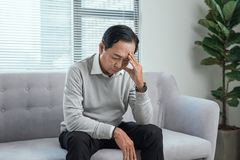 Health care, stress, old age and people concept - senior man suffering from headache at home.  stock image