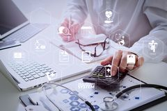 Healthcare costs and fees concept.Hand of smart doctor used a ca. Health care system diagram with health check and symptom on VR dashboard.Healthcare costs and royalty free stock images
