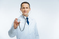 Happy medical worker using stethoscope over light background. Health care and treatment. Selective focus on a face of a mature doctor looking into the camera stock images