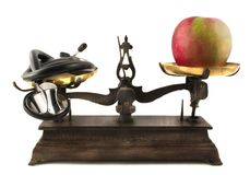 Health Care Weighing You Down. Stethoscope and apple on antique scale Stock Photography