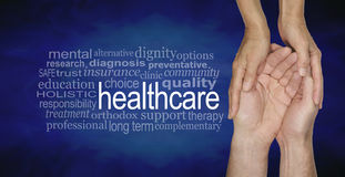 Health Care Word Cloud. Female hands gently cradling male hands on a misty blue vignette background with a healthcare word cloud to the left Stock Photos