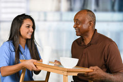 Health Care Worker and Elderly Patient Eating. Health care worker serving a meal to an elderly patient Stock Image