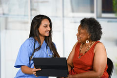 Health Care Worker and Elderly Woman. Health care worker helping an elderly woman Stock Image