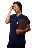 Health care worker with a headache. Young brunette asian woman health care worker wearing blue scrubs with hand on head holding chart looking stressed Royalty Free Stock Photography