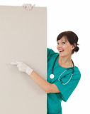 Health care worker woman pointing to blank sign Stock Photos