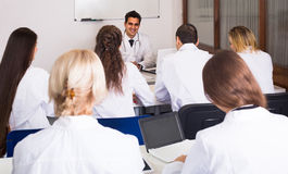 Health-care workers during educational program in school. Adult smiling russian health-care workers during educational program in medical school Stock Image