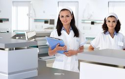 Health care workers at hospital reception. Young health care workers at hospital reception smiling stock image