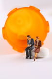 Health Care Worries. Miniature man and woman sitting on pill next to almost empty pill bottle Stock Photo