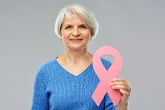 Old woman with pink breast cancer awareness ribbon. Health, charity and old people concept - portrait of smiling senior woman with pink breast cancer awareness royalty free stock photos