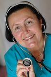 Health checkup with a smile. Older, friendly nurse holding a stethoscope Stock Images