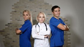 Health clinic concept. Doctors posing. Team of Three young successful medical workers in white and blue unuforms stand. Health clinic concept. Doctors posing stock video footage