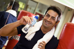 Health club. Athlete relaxing and drinking some water Royalty Free Stock Image
