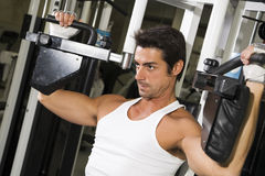 Health club. Guy in a gym doing weight lifting Royalty Free Stock Photos
