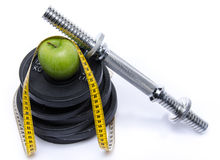 Health concept, an apple with a tape measure and weights Stock Image