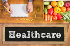 Health Concept: HEALTCARE. With fresh vegetables and  on a wooden table Royalty Free Stock Images