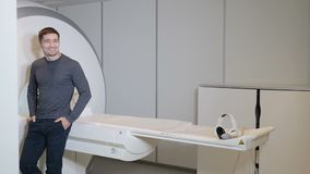 Health concept. hospital patient near MRI, tomograph, scanner, CT machine.Male smiling patient in modern healthcare. Clinic stock video