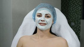 Health concept. Portrait of young woman in facial cosmetic mask in beauty centre. Smiling. Shot in 4 k stock footage