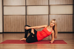Health concept. Young beautiful woman does yoga exercise in the modern room Stock Image