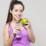 Health concious lady holding fruit and refreshing drink Stock Photography