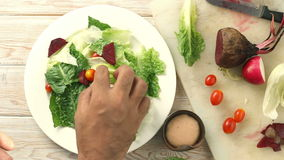 Health conscious hand chef tossing a tasty organic green salad, Top view stock video