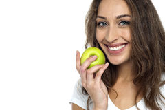 Health conscious woman about to eat fresh green apple. Holding it close to her mouth Royalty Free Stock Images