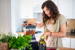 Health conscious woman using a blender Royalty Free Stock Image