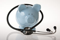 Health Cost. Piggy bank with a stethoscope on a white back ground Stock Images