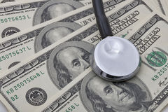 Health costs. Stethoscope on money background of hundred dollar bills Royalty Free Stock Images