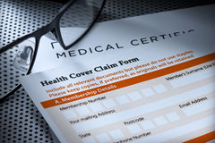 Medical Health Cover Insurance Form. A health cover claim form with reading glasses stock photography
