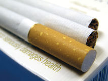Health damage. Cigarettes over pack Royalty Free Stock Photos