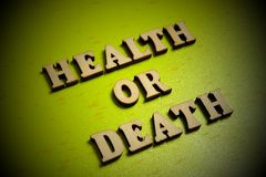 Health or death. Concept The inscription of wooden letters on a green background. Vignetting. Health or death. Concept. The inscription of wooden letters on a stock images
