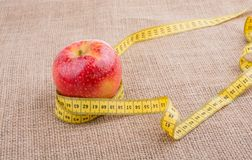 Red apple with a measurement  tape on it Royalty Free Stock Photography