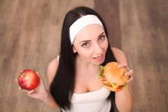 Health, diet and food concept - healthy woman smelling hamburger and holding apple Royalty Free Stock Photos