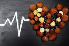 Health diet heart concept with berry and pulse on black background. Health diet heart concept with strawberry, blueberry, raspberry, and pulse on black stock photos