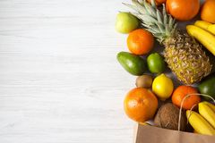 Health diet. Paper bag of different fruits on white wooden background. Flat lay. Top view. Copy space stock image