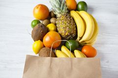Health diet. Paper bag of different fruits on white wooden background. Flat lay. Top view stock photography