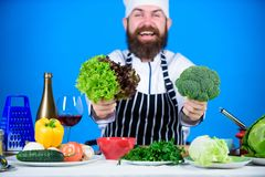 Health and dieting. Man cook hat apron hold broccoli and lettuce. Vegan recipe concept. Buy fresh vegetables grocery. Store. Vegan restaurant. Hipster chief stock photos