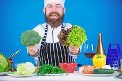 Health and dieting. Man cook hat apron hold broccoli and lettuce. Vegan recipe concept. Buy fresh vegetables grocery. Store. Vegan restaurant. Hipster chief royalty free stock photography