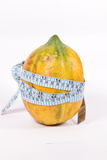 Health & Fitness. Papaya & Measuring Tape on plain  background Royalty Free Stock Photography