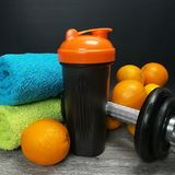 Health and fitness stuff with orange and weights. Health and fitness theme, healthy fruits isolated on black background Stock Photo