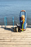 Health, fitness, yoga. Leisure and relaxation in the coast, the girl spends his free time, she sits on the pier overlooking the water, vertical royalty free stock photos