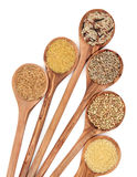 Health Food. Healthy food of brown and wild rice, bulgur wheat, couscous, rye grain and  buckwheat grain in olive wood spoons over white background Royalty Free Stock Images