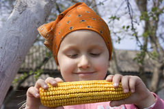 Health food. On the image there is a little girl. She eat corn stock images