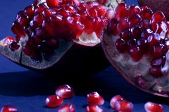 Close-up on a red garnet. fruit pieces of pomegranate on a dark background stock photo