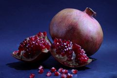 View of red juicy pomegranate fruit on a dark blue background of dark table. Health food for fitness concept with pomegranate fruit royalty free stock image