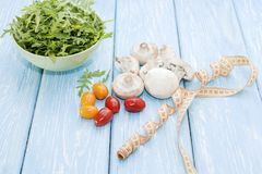 Health food. Fresh mushrooms and arugula salad, cherry tomatoes on light blue background. Diet meals. stock photos