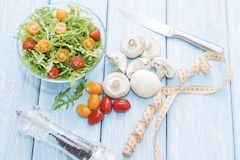 Health food. Fresh mushrooms and arugula salad, cherry tomatoes on light blue background. Diet meals. stock photography