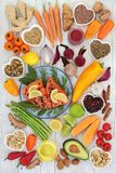 Health Food for Heart Fitness. Concept with super foods of salmon fish, fruit, vegetables, seeds, nuts, spice and herbs used in herbal medicine and providing royalty free stock images