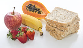 Health food. Mix of fruits and bread on white background Stock Photos